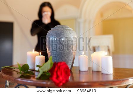 cremation, people and mourning concept - cinerary urn and woman crying at funeral in church