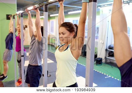 sport, fitness, exercising and training concept - group of people hanging at horizontal bar in gym