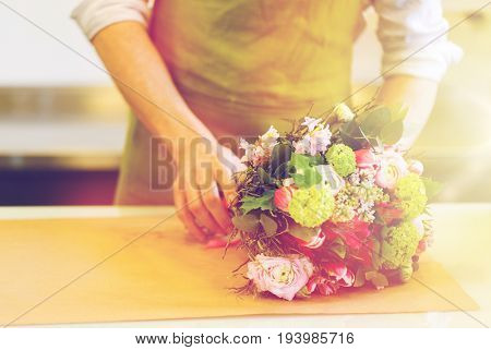 people, shopping, sale, floristry and consumerism concept - close up of florist man wrapping flowers in paper at flower shop