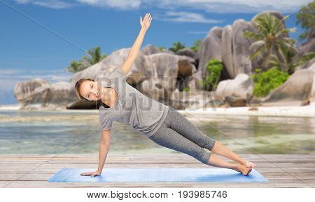fitness, sport and people concept - woman doing yoga in side plank pose on mat over exotic tropical beach background