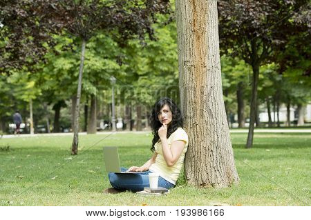 Attractive latin woman wearing casual clothes working and studying on her laptop and tablet in a lush green park working studying female laptop sitting outdoor latin person park girl notebook internet woman beautiful modern lifestyle business computer wor