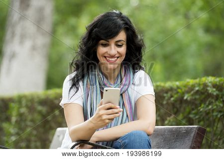 Happy Attractive Latin Woman Talking And Texing On Her Smart Phone.