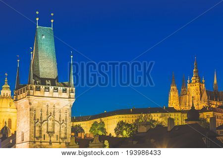 Prague Castle in Mala Strana district and Charles Bridge Tower during blue hour sunset in Czech Republic.