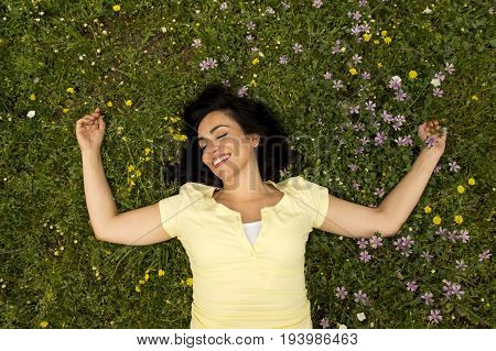 Happy Beautiful Latin Woman Lying On The Green Grass Sleeping And Meditating