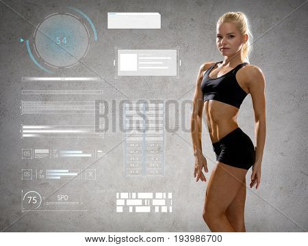 sport, fitness, bodybuilding, weightlifting and people concept - young woman in sportswear posing and showing muscles over gray background