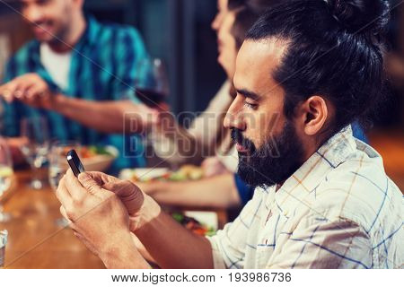 leisure, technology, internet addiction, lifestyle and people concept - man with smartphone and friends at restaurant
