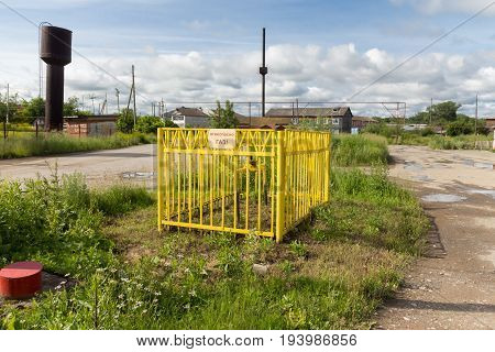 The gas valve is enclosed by a fence with a yellow sign
