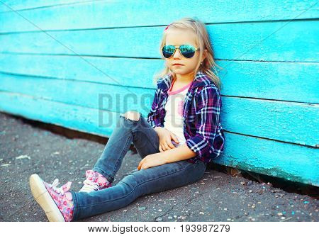 Fashion Child Wearing A Sunglasses And Checkered Shirt Sitting In The City