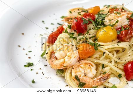 Seafood. Spaghetti pasta with prawns or shrimps with mixed colours cherry tomatoes fresh parsley and pepper.