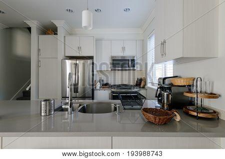 Modern white kitchen with stainless steel appliances. Interior design.