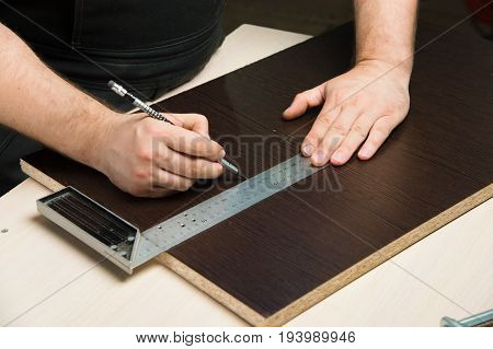 Men's hands draw a pencil on the ruler with a sub-standard template for cutting out furniture details