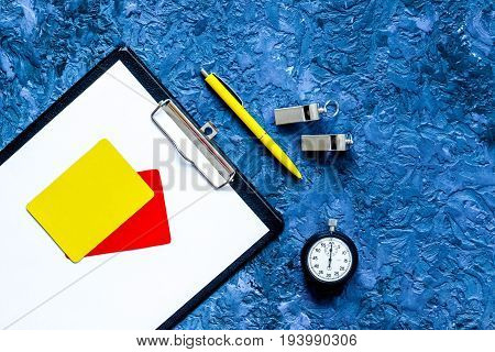 Set to judge competition. Yellow and red cards, stopwatch, whistle, pad on blue table background top view.