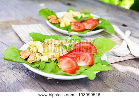 Fresh salad with cucumbers, tomatoes, salad leaves, cheese and walnuts in a plate, selective focus