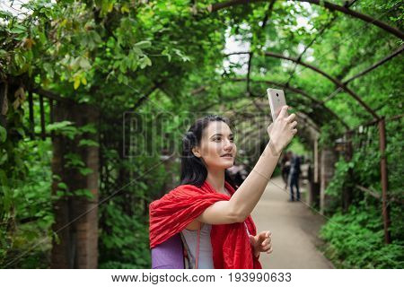 Portrait of young attractive woman doing selfie on phone outdoors. Selective focus on phone