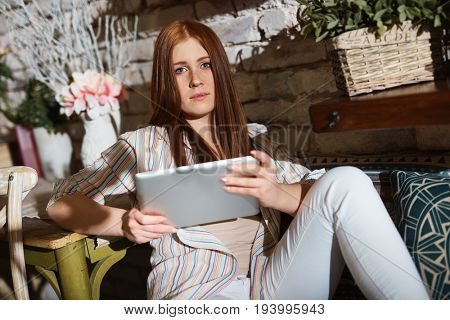 Young ginger woman using tablet computer at home.