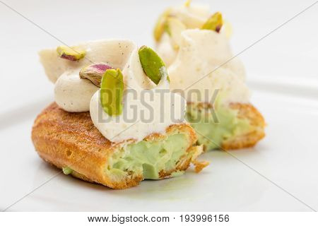 Cut Eclair With Vanilla Cream And Pistachio