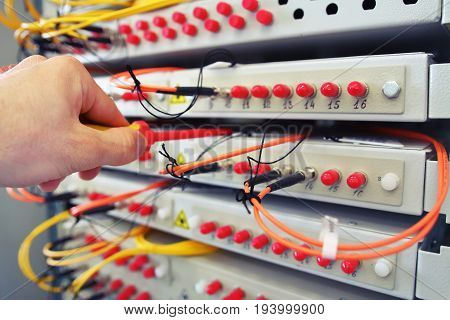 Adjustment fiber optical switch with connected FC cables in server room. Optical fibre information technology equipment in data center
