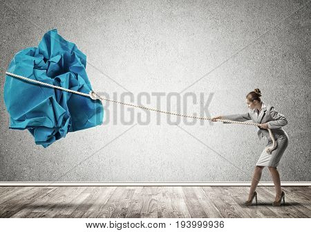 Young woman making huge paper ball move