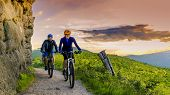 Mountain biking women and man riding on bikes at sunset mountains forest landscape. Couple cycling MTB enduro flow trail track. Outdoor sport activity. poster