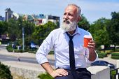 Bearded sir drinking coffee and enjoying panorama of city  poster