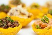 Plantain cups filled with different types of stuffing on white background poster