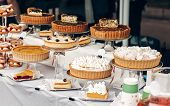 delicious cakes and pie with whipped cream on table at street food festival. candy bar with tasty sweets catering at wedding reception. open kitchen outdoors. summer picnic poster