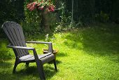 Simple adirondack chair on grassy area with potted plant and hanging basket of flowers quiet place for solitude and thinking beautiful soft sunlight and shadow poster