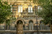 Facade of old building of multi-colored tufa stone with carved archescolumns and cornices surrounded by trees poster