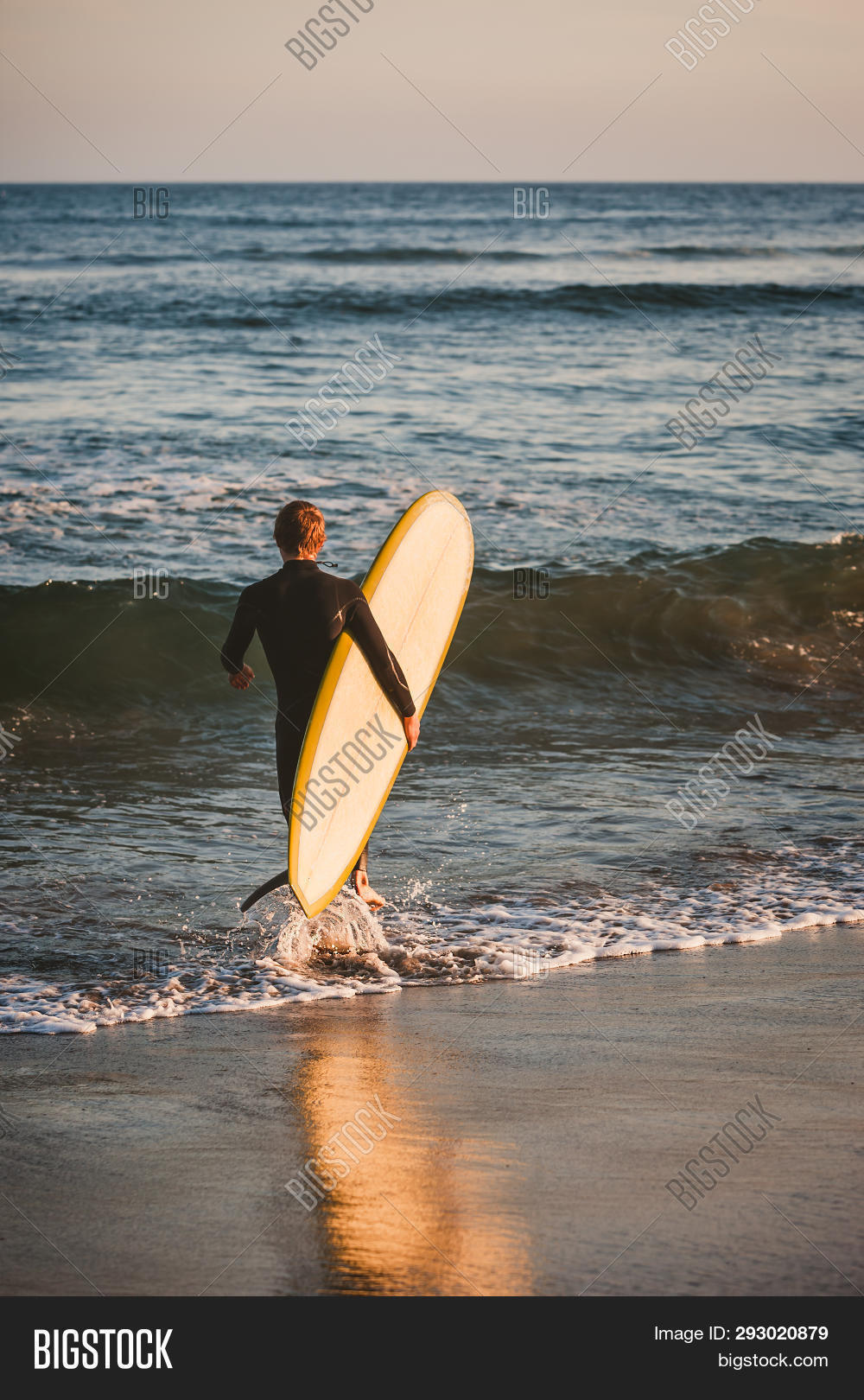 Young Boy In Black Wetsuit Carries His White And Yellow Surfboard Out To Catch Some Waves In The Pac