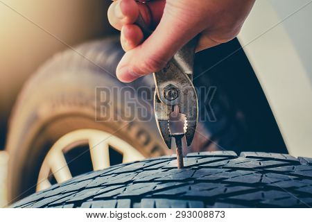 Hand Pulling For Removing A Nail In The Tire, Flat Tire Fixing And Repair The Tire Is Leaking From T