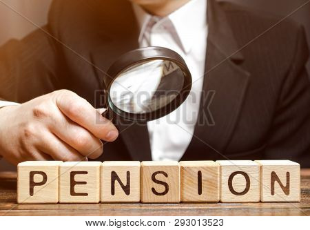 Wooden Blocks With The Word Pension And A Magnifying Glass In The Hand Of A Man. Analysis Of Retirem