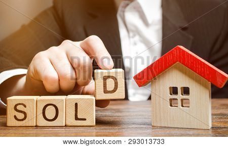 A Realtor Holds Blocks With The Word Sold Near A Miniature Wooden House. Real Estate Market. Selling
