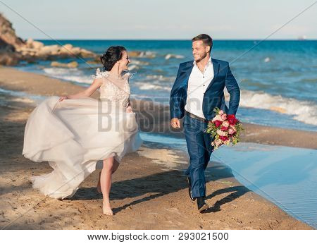 Lovely Wedding Couple, Groom And Bride, Are Walking In The Shore Of The Sea, Running, Laughing, Havi