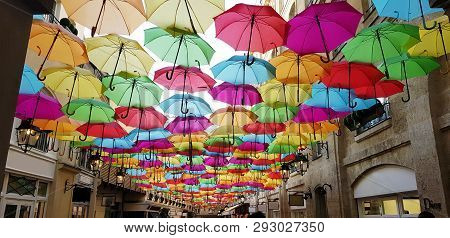 Street Installation Of Multi-colored Open Umbrellas. The Sky Of Colorful Umbrellas. Background Color