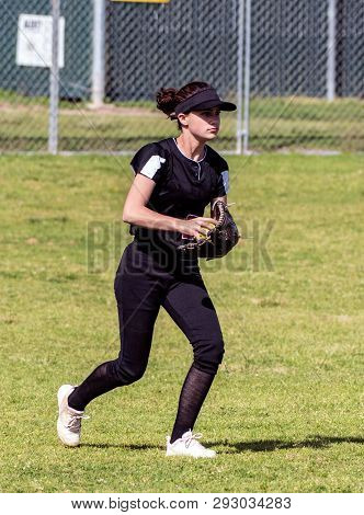 Skilled Teenage Softball Player Alert For The Next Play After Making A Defensive Catch In The Outfie