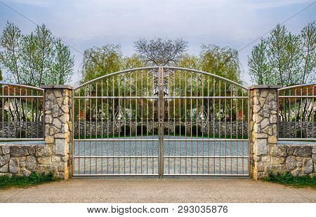 Chrome Fence Gate. Chromium Stainless Steel Fence On Stone Wall