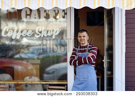 A Handsome Young Coffee Shop Owner Standing In The Entrance Of His Shop. Coffee Shop Inscription On