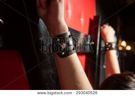 Female Hands Chained To Cross With Handcuffs