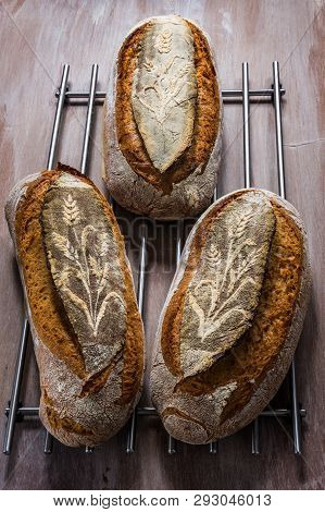 Three Loaves Of Bread With Ears Of Wheat Design