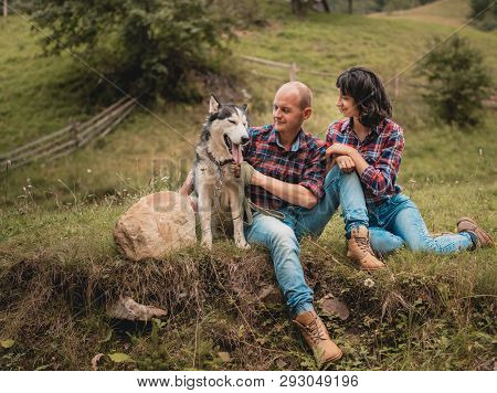 Portrait of nice lovely cute couple with husky dog having fun on summer vacation. Portrait of a happy couple hugging. Summer holidays, love, relationship concept - smiling couple with dog husky in mountains.