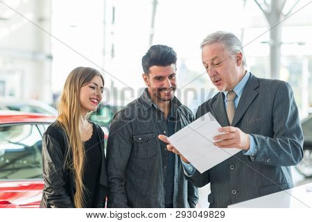 Car dealer new car concept, salesman selling a car tp a young couple
