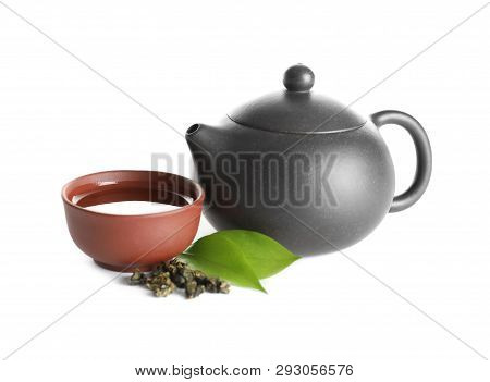 Teapot Near Cup Of Tie Guan Yin Oolong And Leaves On White Background