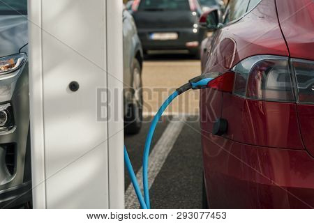Electric Car Connected To A Recharging Pole. Concept For Environmental Awareness.