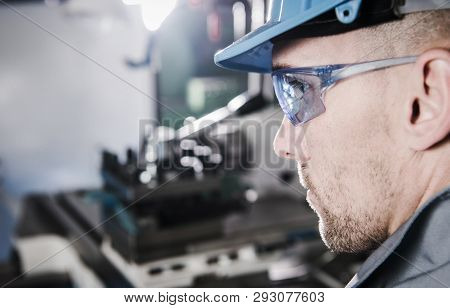 Caucasian Industrial Worker Wearing Safety Glasses And Hard Hat. Closeup Photo.