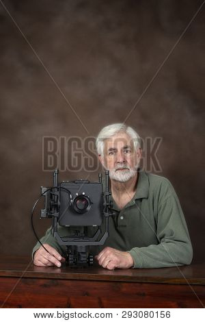 Vertical Shot Of An Elderly Photographer Sitting Behind A Professional View Camera.  Brown Backgroun