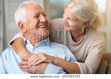 Portrait of happy senior couple sitting on sofa at home