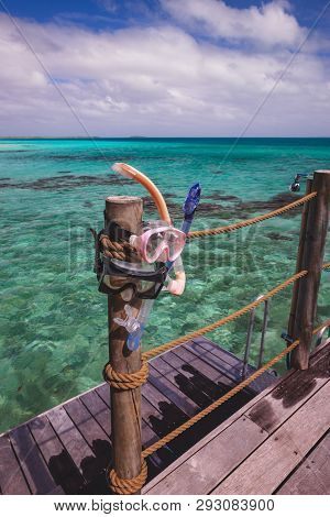 Two Snorkel Masks Drying Out On A Wooden Pillar Next To A Shower On The Deck Of An Over Water Bungal