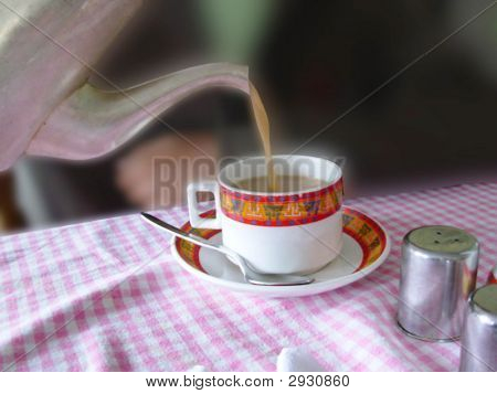 Tea being poured in a cup by a man.