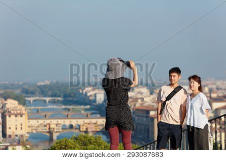 FLORENCE, ITALY - AUGUST 9, 2018: Chinese tourists make photo from the Piazzale Michelangelo against the cityscape of Florence. Created in 1869, the square is famous for its panoramic view to the city