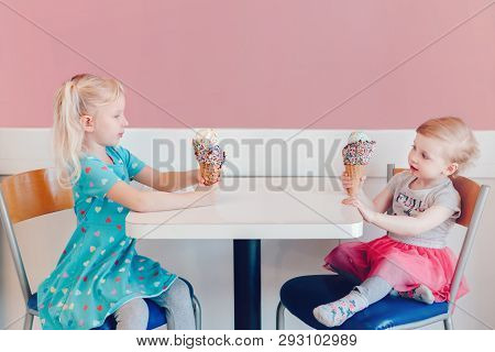 Lifestyle Portrait Of Two Happy Caucasian Cute Adorable Funny Children Girls Sitting Together Braggi